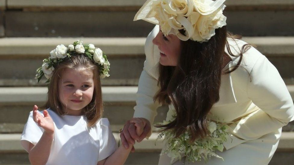 Princess Charlotte waves to the crowds, as she holds her mother, the Duchess of Cambridge's, hand