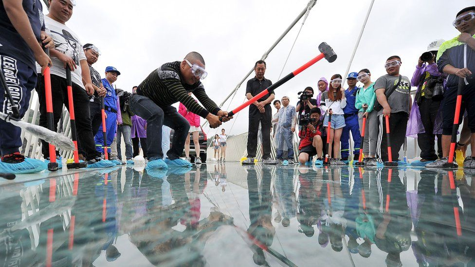 A man swings a sledgehammer at the floor of the glass bridge
