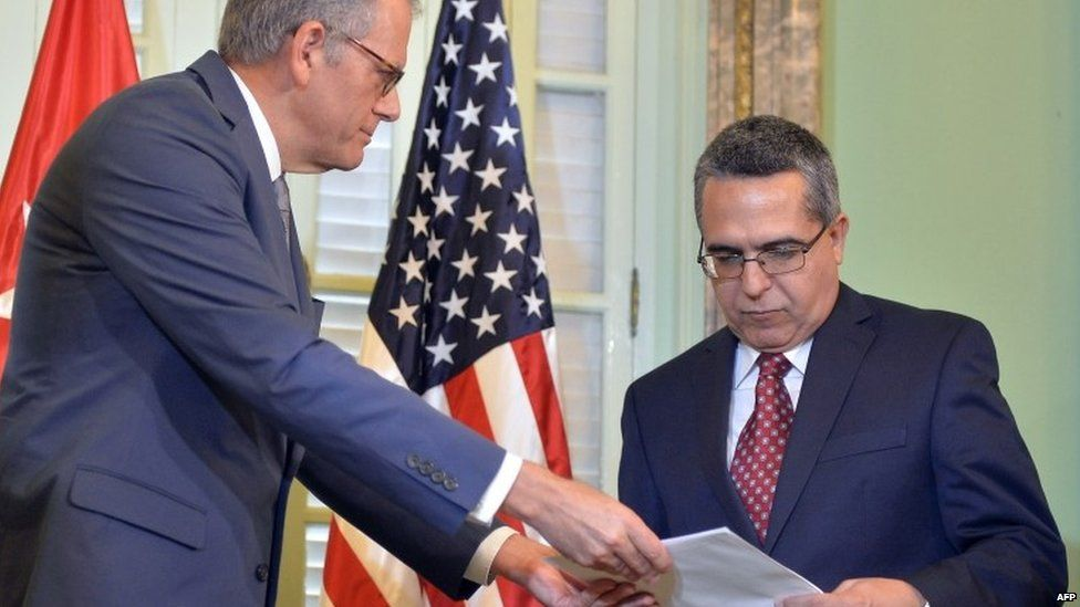 The head of US Interest Section, Jeffrey DeLaurentis (L), gives Cuban Foreign Vice-Minister Marcelino Medina a letter from US President Barack Obama to Cuban President Raul Castro