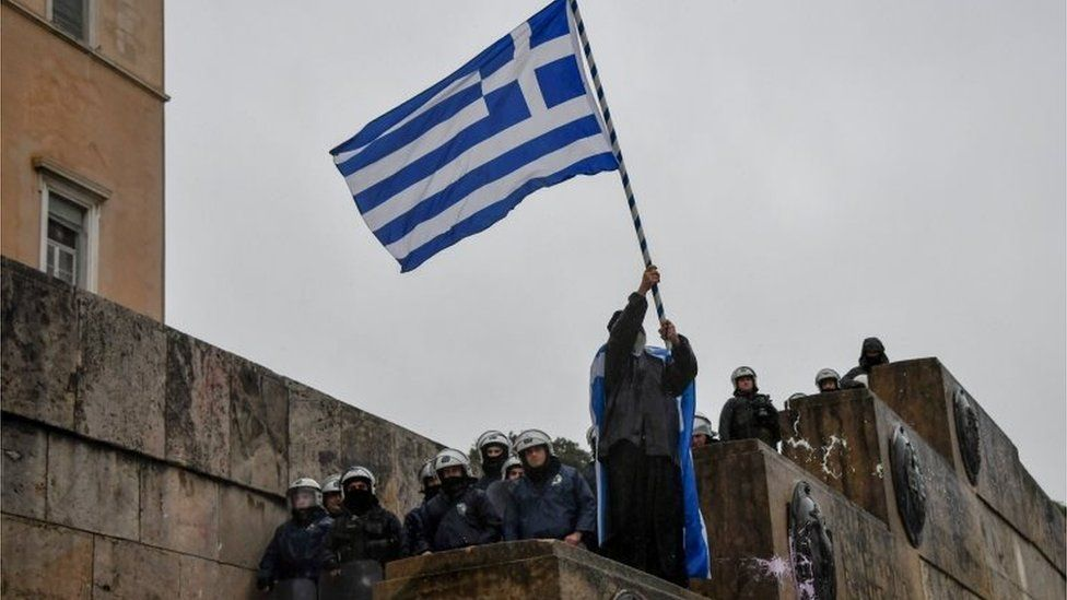 An Orthodox monk waves a Greek national flag next to riot police