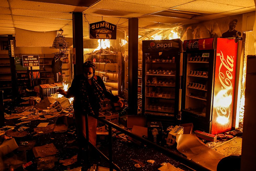 A woman reacts while protesters set fire in a liquor store