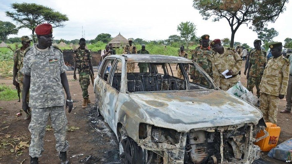 South Sudanese SPLA soldiers inspect a burned out car in Pageri in Eastern Equatoria state on August 20, 2015.