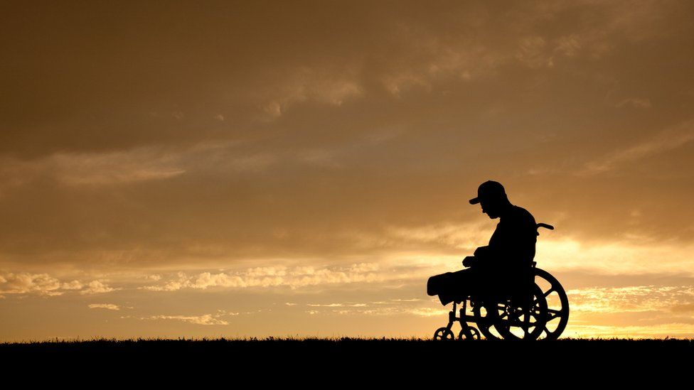 A disabled man with his head bowed
