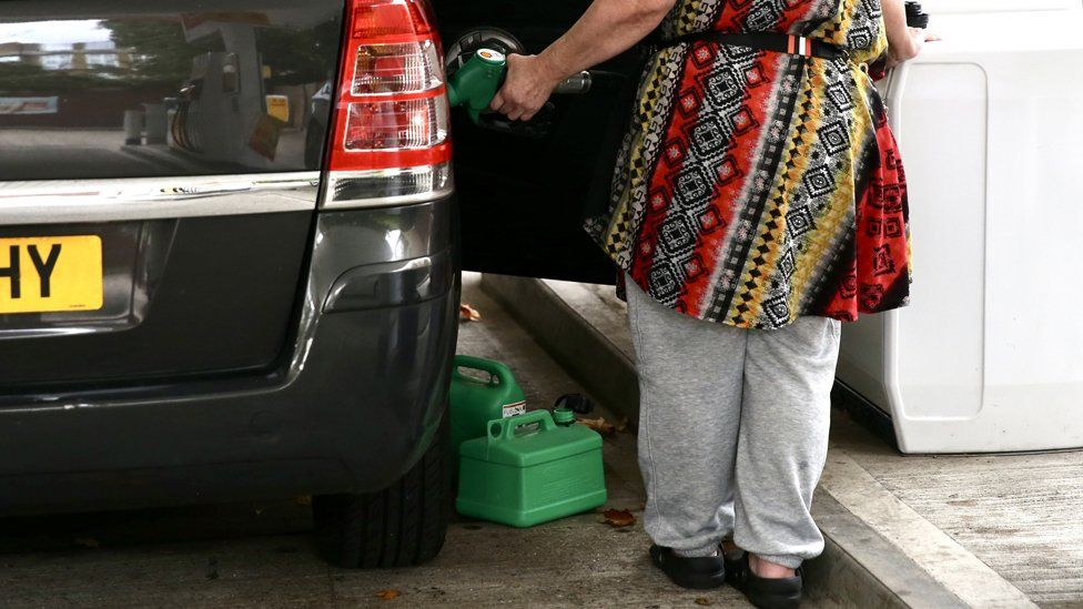 A woman fills her car with fuel alongside two jerry cans at forecourt in London