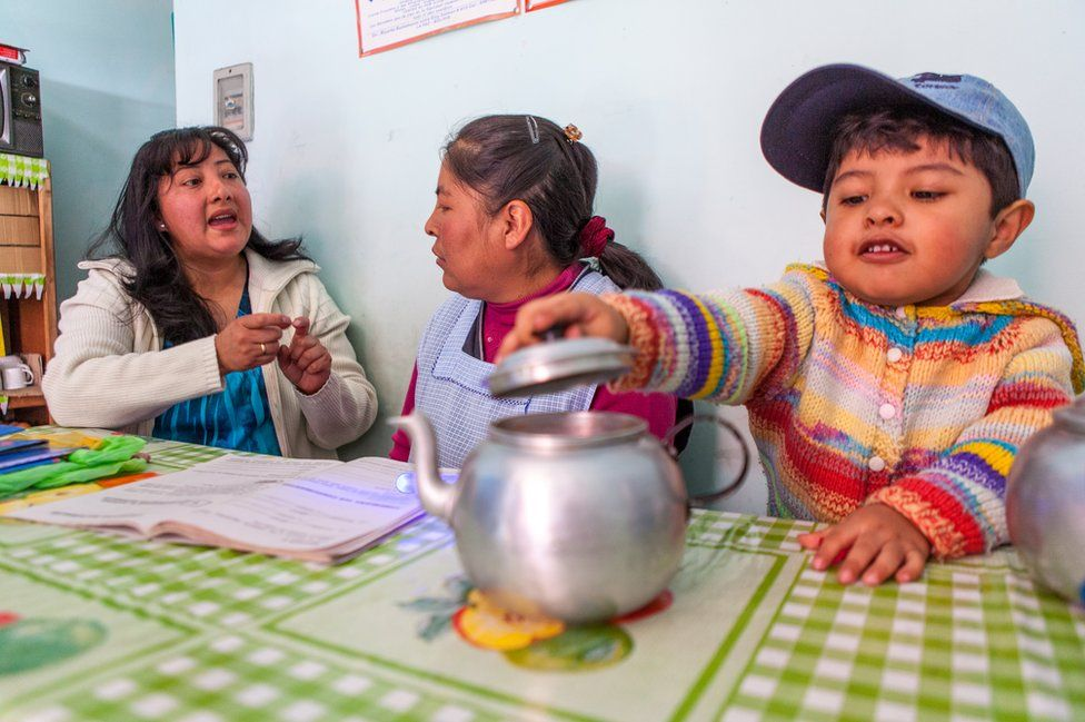Ms Guzman teaching a mother whose child is playing with a tea pot