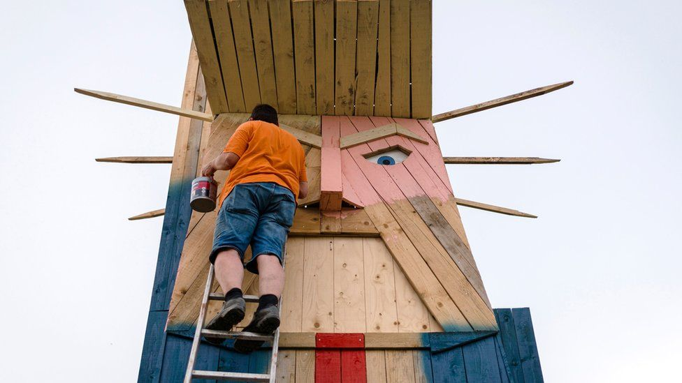 People work on a wooden statue made to resemble US President Donald Trump in the village of Sela pri Kamniku in August 2019