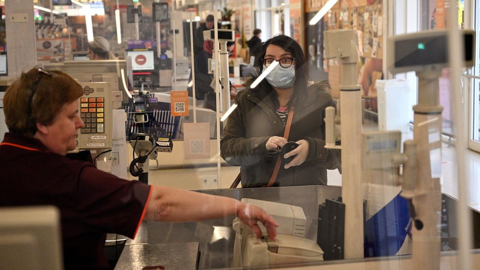 A supermarket worker behind a protective screen