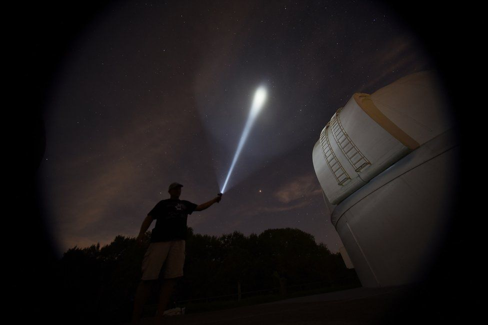 Person shining a torch at the night sky