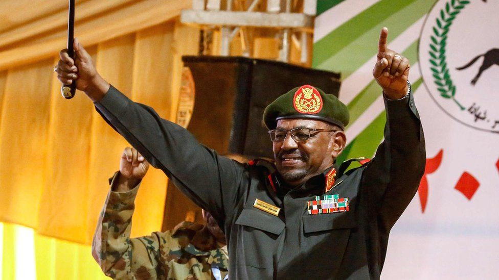 President Omar al-Bashir holds his arms aloft in Sudan while addressing supporters