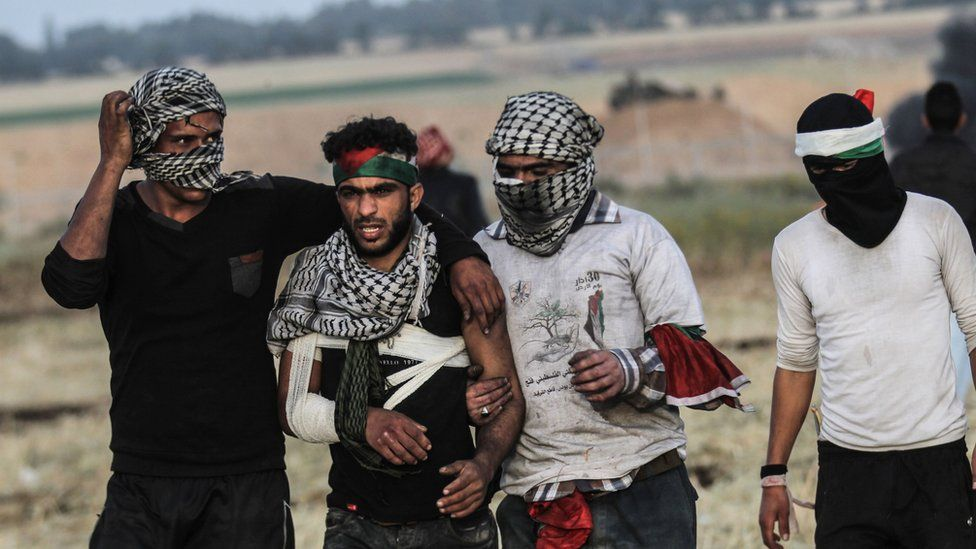 Palestinian protesters help a man injured during clashes with Israeli forces near the border with Israel on April 2, 2018
