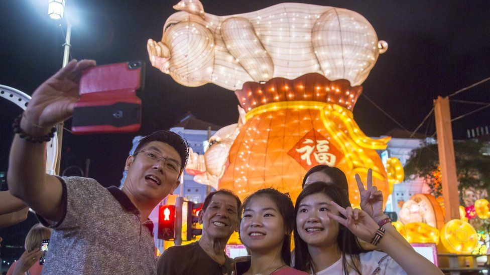 A family pose for a photo in front of a light display in Chinatown on the eve of the Lunar New Year of the Pig