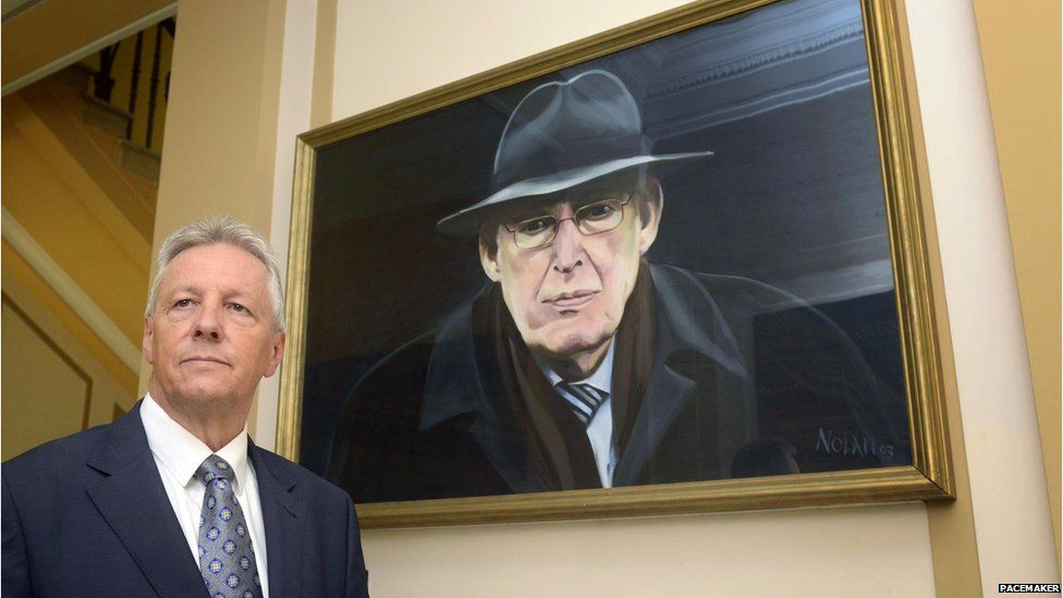 Mr Robinson beside a portrait of his predecessor as DUP leader Ian Paisley