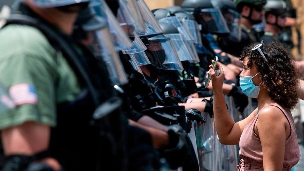 A protester hold up her phone to show a line of police in riot gear something on the screen