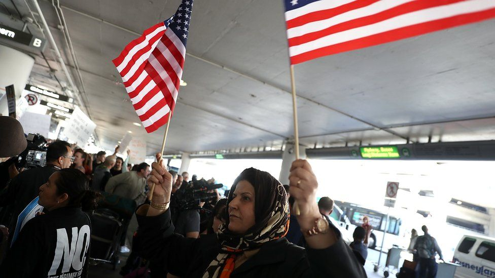 A protester waves American flags during a demonstration against the immigration ban in January 2017 in Los Angeles, California