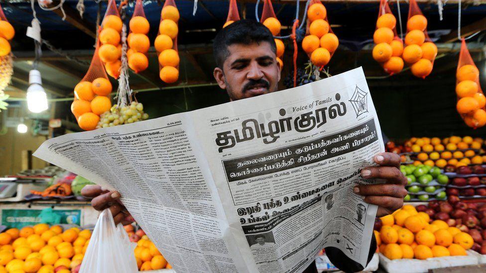 Man reading Tamil language paper