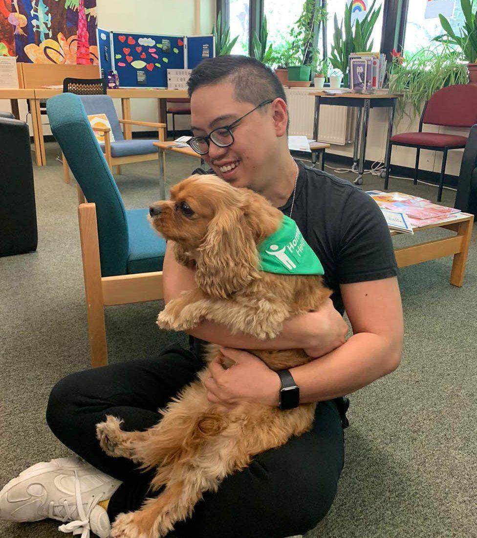 Alfred hugging a dog
