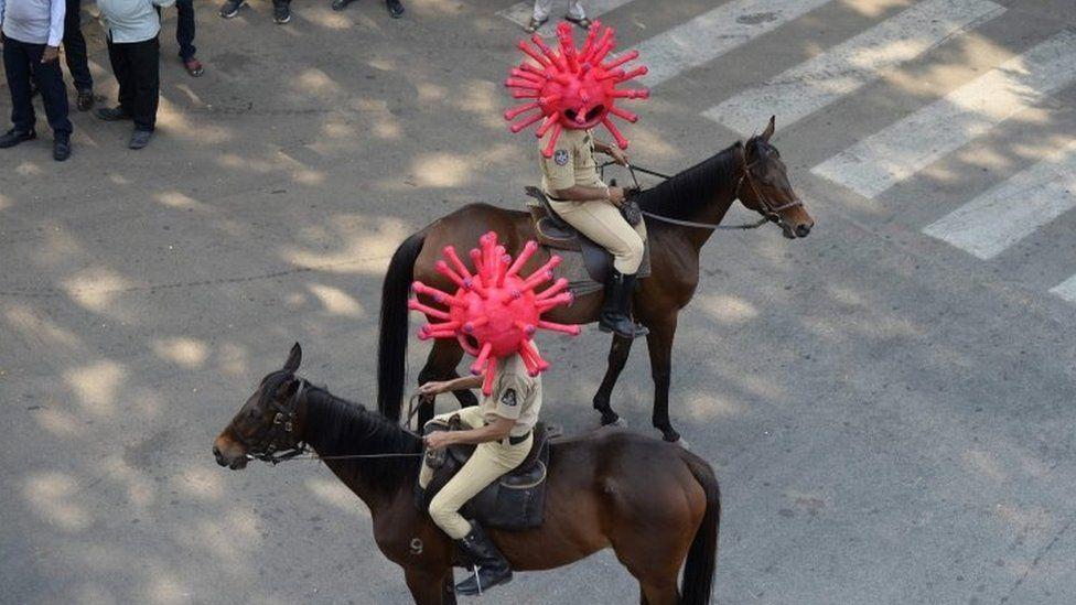 Police on horseback wearing virus helmets