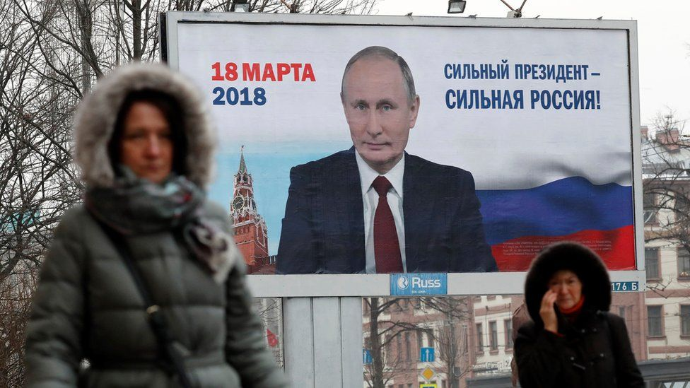 Women pass a Putin election poster in St Petersburg, Russia, 12 January