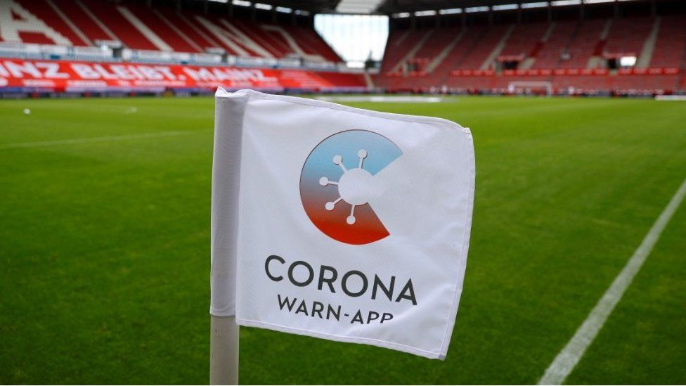 An advert for the contact tracing app on the corner flags at Mainz