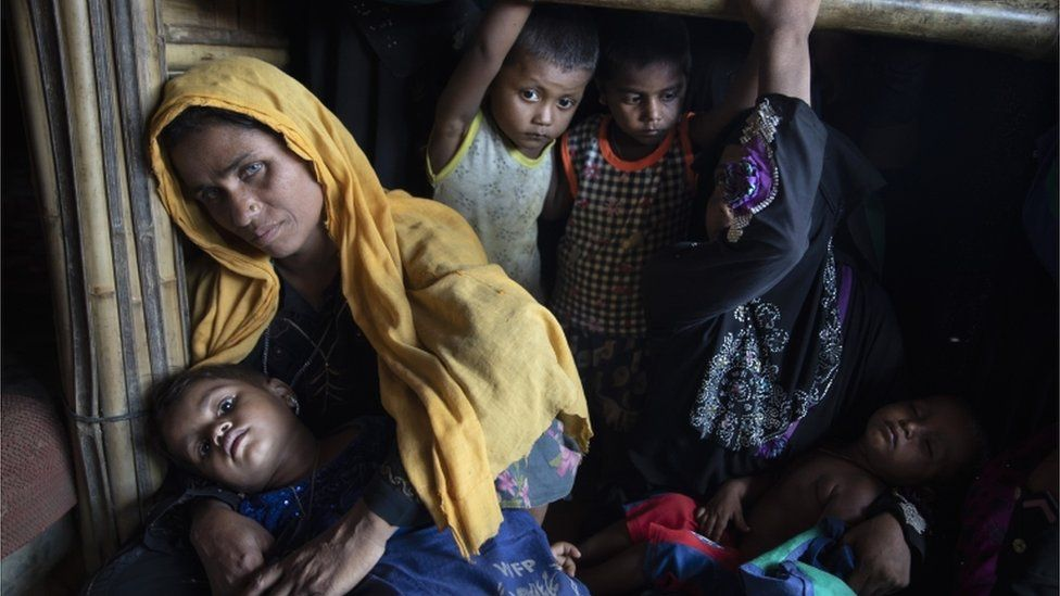 """Rohingya women and children wait in line for a food distribution in Kutupalong camp on August 26, 2018 in Cox""""s Bazar"""