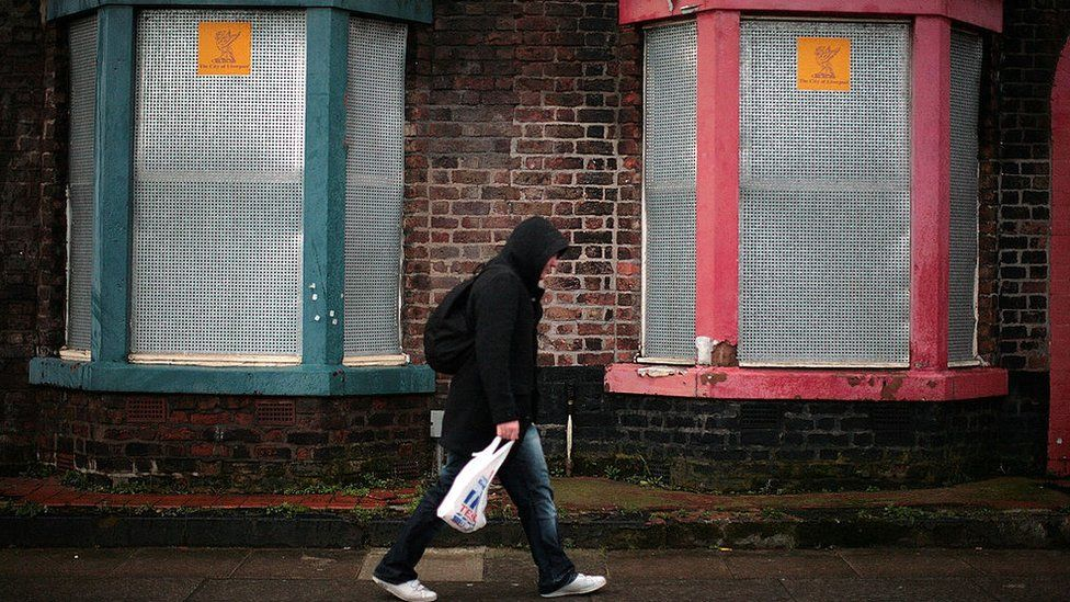 Man walking past some boarded up houses