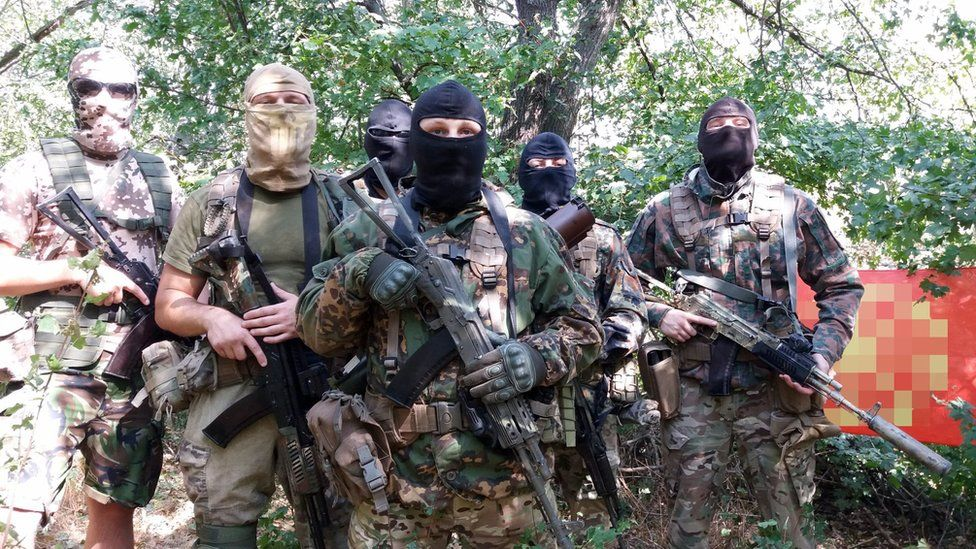 A picture of four men dressed in camouflage and holding guns