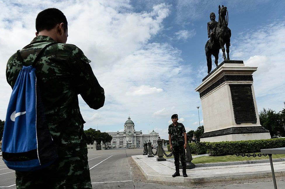 Soldiers take pictures in front of King Rama V statue and Ananta Samakhom Throne Hall the day after the controversial constitutional referendum in Bangkok on 8 August 2016.