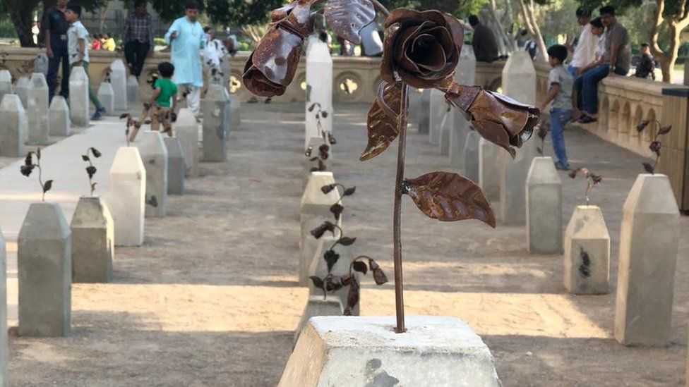 """A bronze rose sits on top of the """"gravestone"""""""
