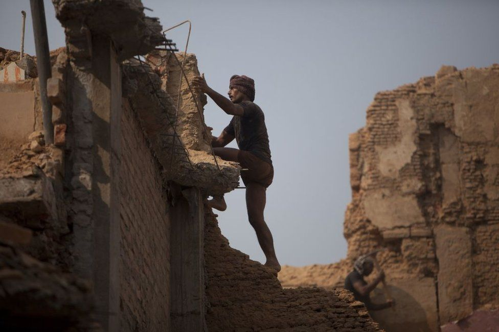 An Indian labourer climbs the wall of a building undergoing demolition in in Uttar Pradesh state.