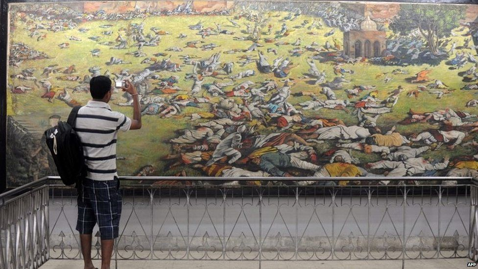 An Indian man takes a photograph of a painting depicting the Jallianwala Bagh massacre in Amritsar on April 12, 2011