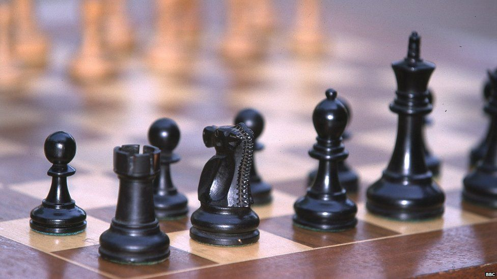 Chess pieces on board. Black pieces, rook, knight, bishop, king and pawns.