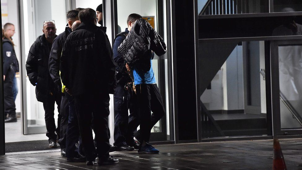 A man is led away by police with a coat hanging over his face