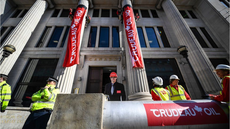 Greenpeace activists scaled two entrance pillars to drop banners at the Canadian High Commission