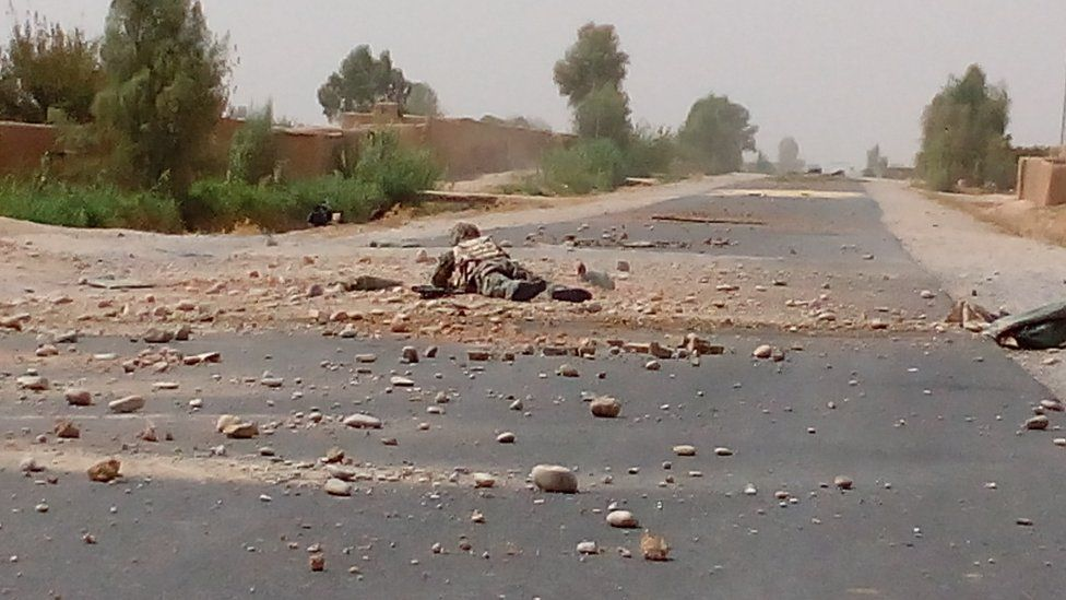 A soldier extracting an IED on the road to Nad Ali District