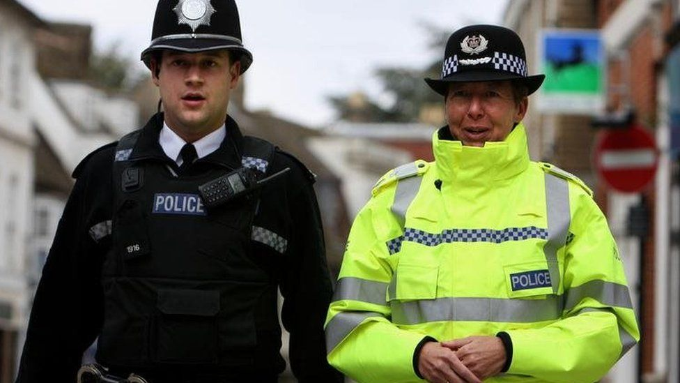 a police Chief Constable walks alongside a police officer