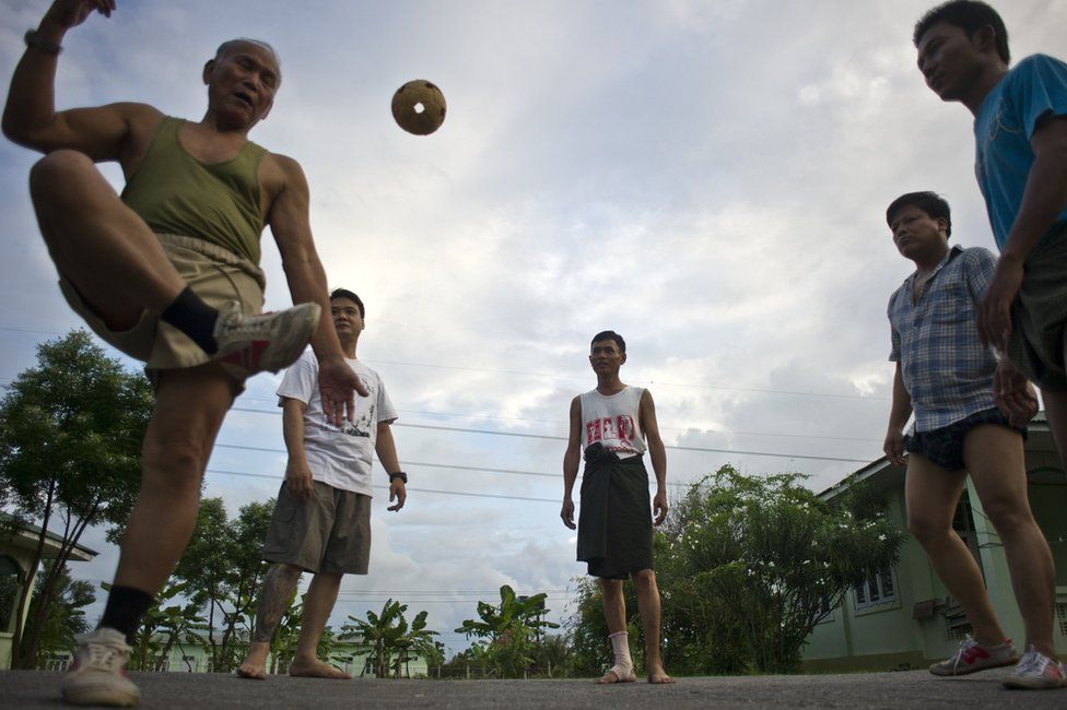 Men playing chinlone in the street