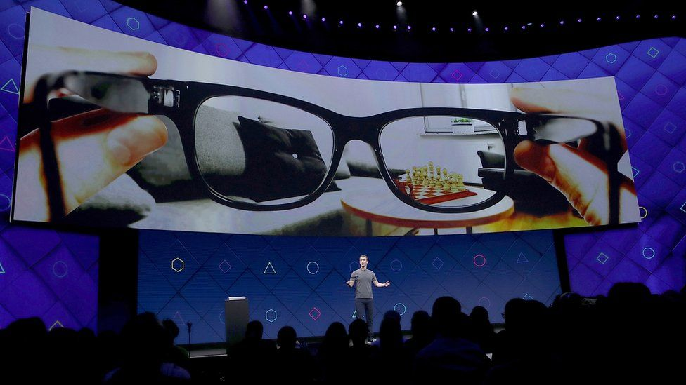 Mark Zuckerberg on stage with a large screen above him showing a pair of glasses.