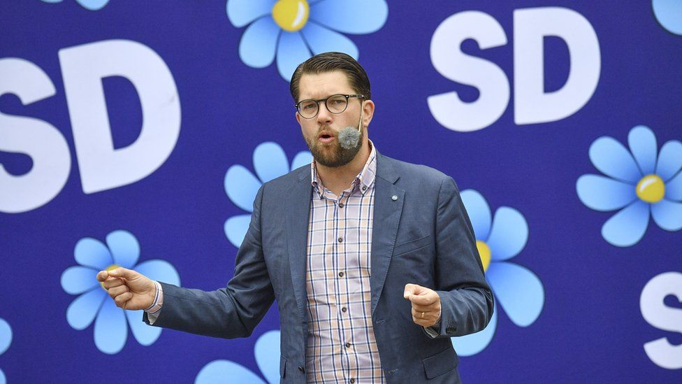 Jimmie Akesson, leader of SD, is photographed in front of the party's floral logo