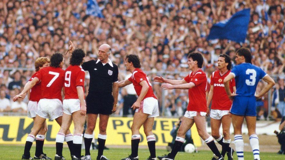 Kevin Moran and various Manchester United players surround referee Peter Willis during the 1985 FA Cup final