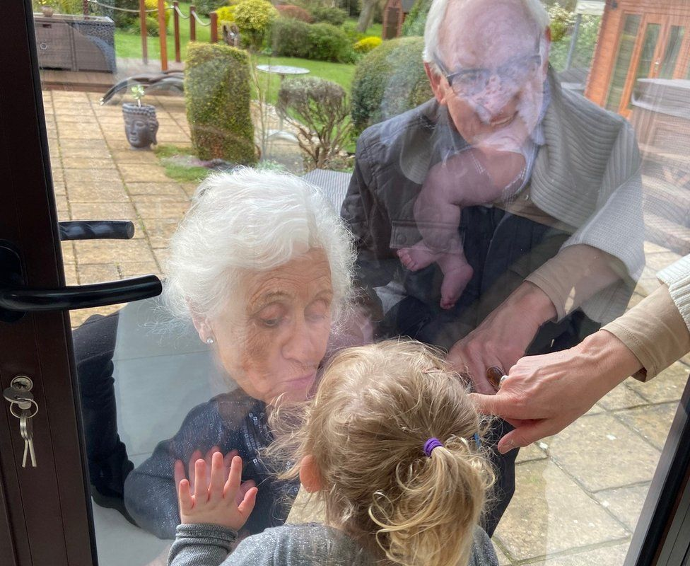 The grandparents kissing their great-grandchildren through the glass