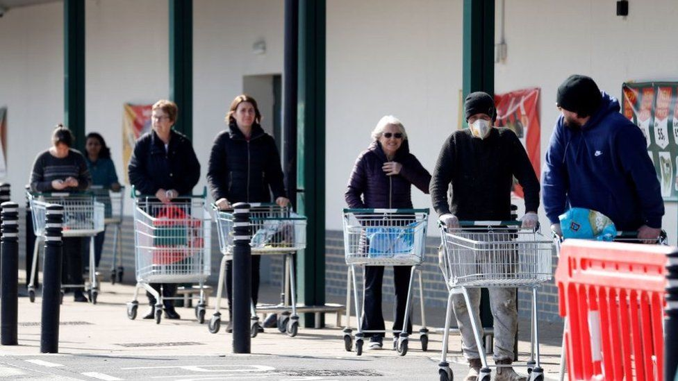 People queueing outside a supermarket