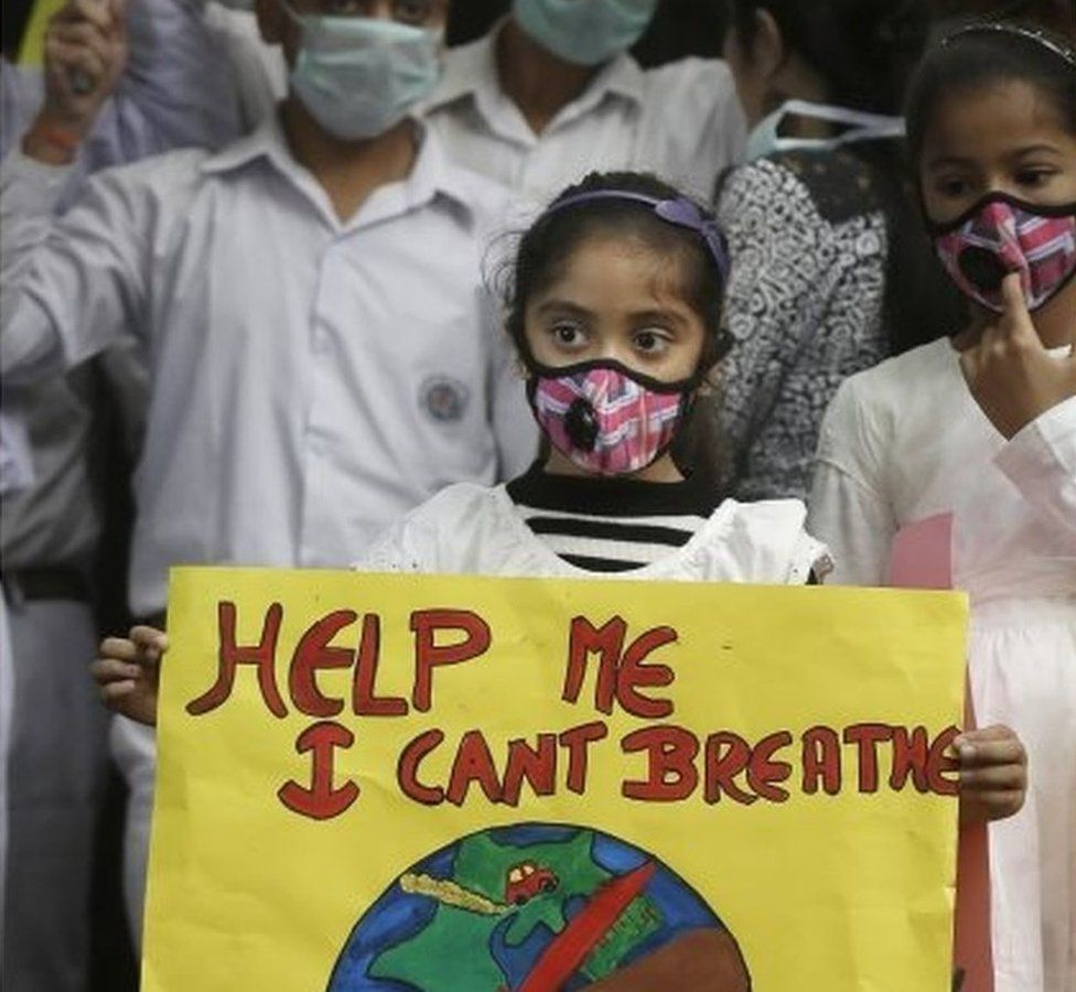 Holding a poster, a girl wears wearing a face mask during a protest against air pollution in New Delhi, India, Sunday, Nov. 6, 2016.