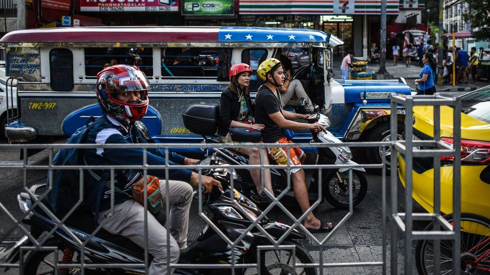 Filipinos at a traffic light in Manila