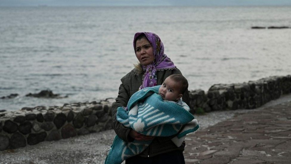 A migrant woman carries a toddler on Lesbos