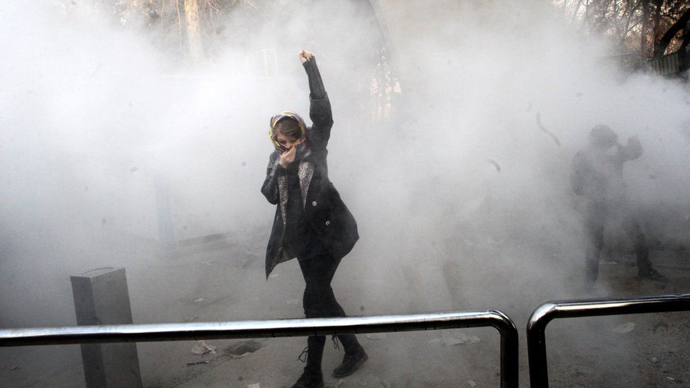 An Iranian university student raises her fist in a cloud of smoke at Tehran University