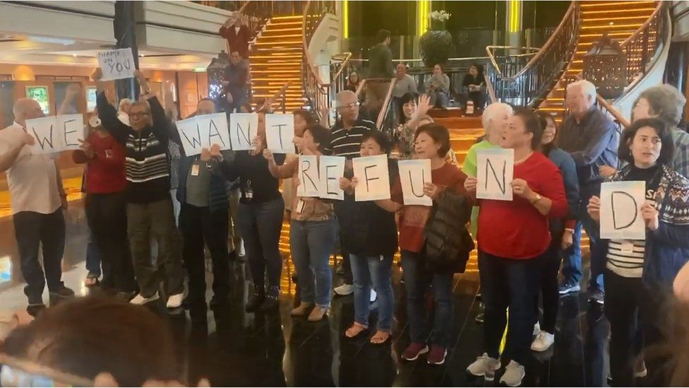 """Passengers crowd hold signs spelling out """"we want refund"""""""