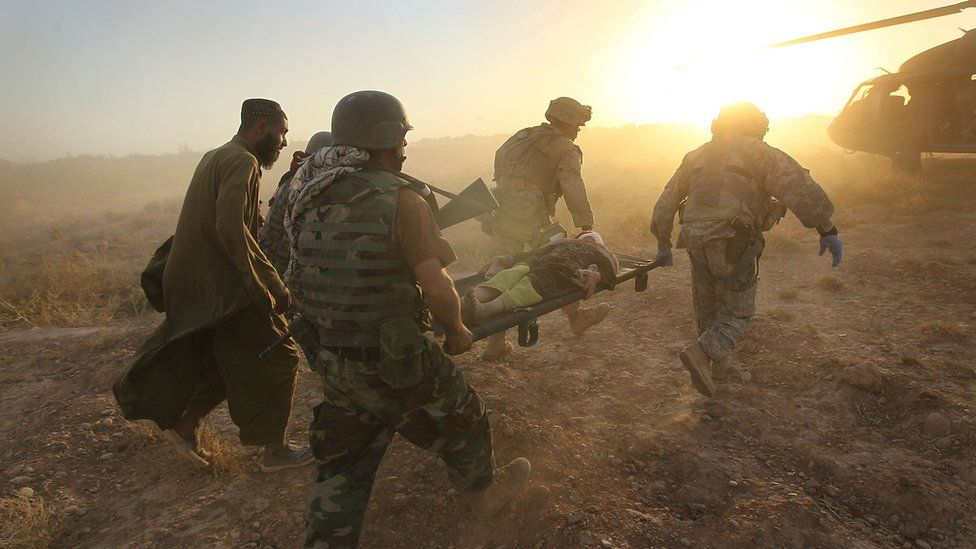 Coalition forces tend to the wounded during fighting near Marja, Afghanistan, in 2010