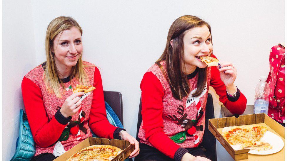 Dwy chwaer Non a Lois Williams o Glwb Bodedern yn bwyta pizza gefn llwyfan