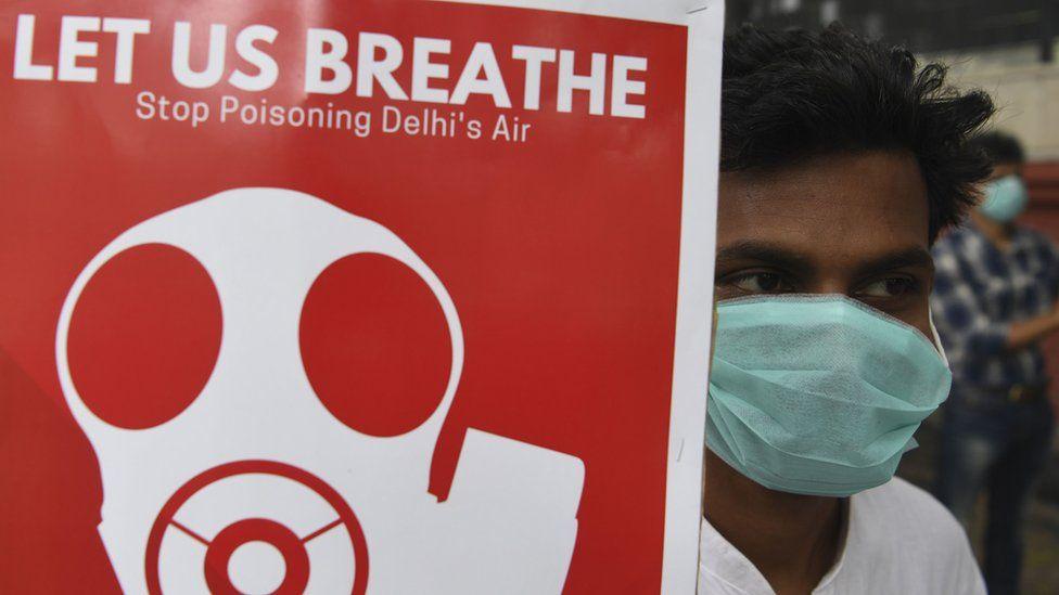 A demonstrator in Delhi holding a sign reading: Let us breathe
