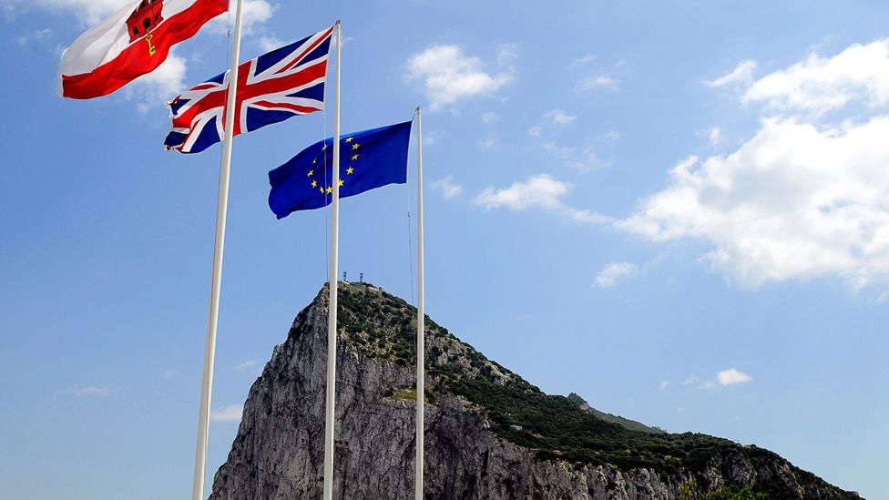 Flags of Gibraltar, Union and EU flying above the rock of Gibraltar